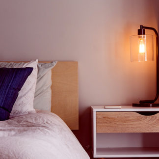 Double bed piled with cusions and a bedside lamp