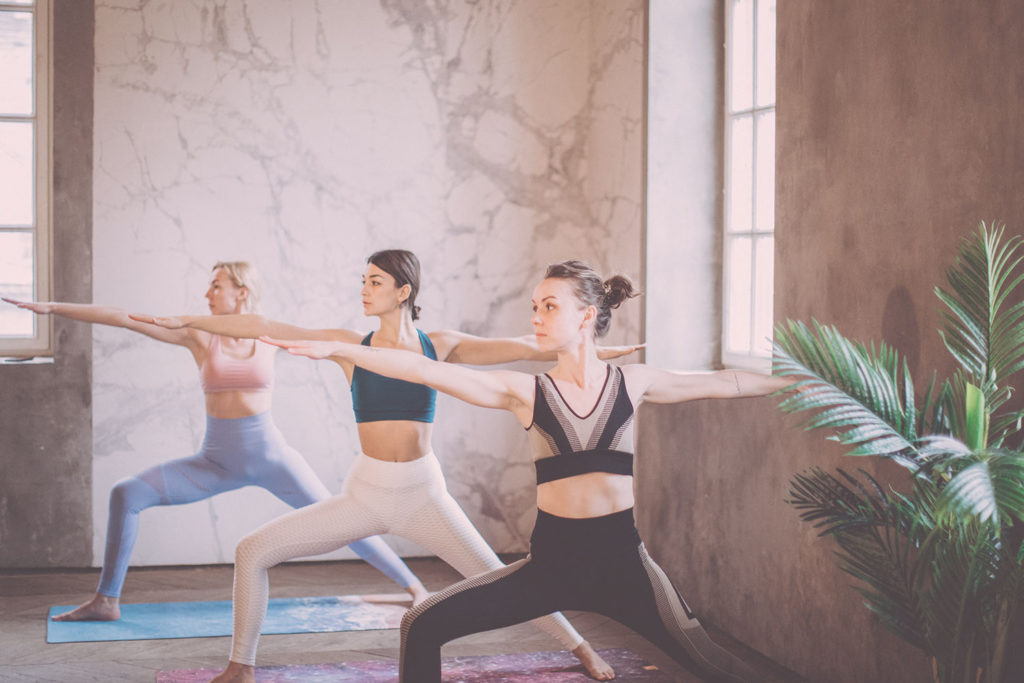 Women performing Warrior II pose in a yoga class